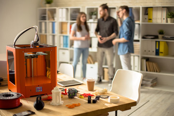 Portrait of three creative young people working in modern design studio, focus on 3D printer on table in foreground, copy space