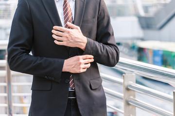 Portrait of handsome man in black suit standing outdoors