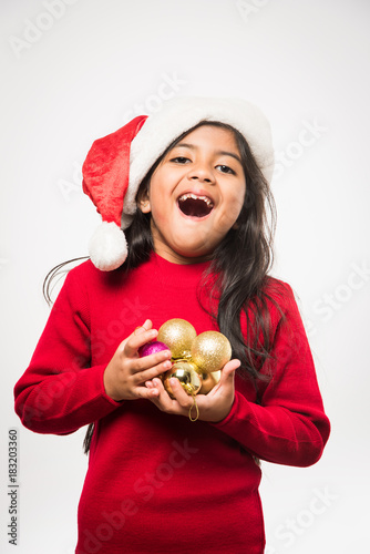 Little smiling Indian girl with christmas gifts while