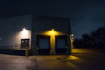 Wall Mural - Dark and scary city warehouse loading dock and entrance door at night.