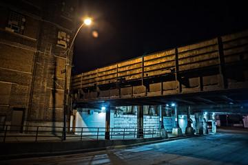 Fototapete - Dark Chicago city street with an industrial urban train bridge underpass at night.
