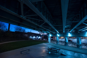 Gritty dark Chicago highway bridge underpass and city street with traffic and a bench at night.
