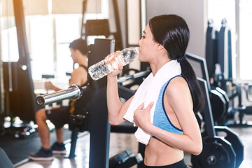 Sporty woman holdind water bottle with towel at the gym.fitness and lifestyle concept