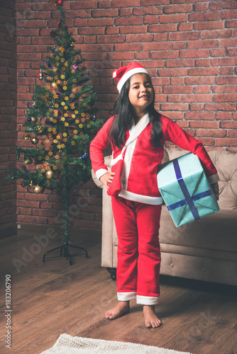 Little Indian girl holding christmas gifts in red cloths or santa