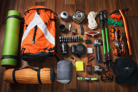 climbing equipment: rope, trekking shoes, crampons, ice tools, ice ax, ice screws, set on dark wooden background, top view.