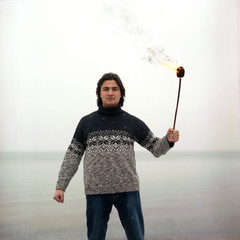Mixed race latin hispanic man with fire torch in warm sweater background of frozen sea. Snow falling in foreground.