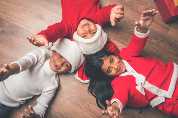 christmas, winter holidays, childhood, friendship and people concept - 3 happy indian children making lying on floor in circle over wooden background with santa hat
