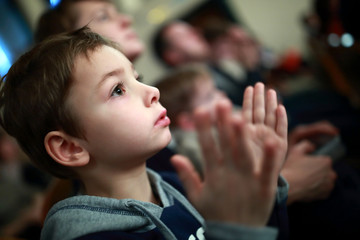 Boy applauding in theater