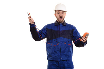 surprised electrician engineer in helmet and uniform with tester