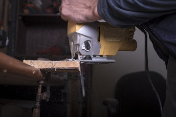 Amateur carpenter uses the jigsaw tool