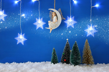 Christmas trees, snowflakes silver garland light, fairy on the moon over the snow and blue background.