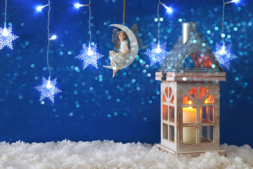 Wooden old house with candle and fairy on the moon over the snow and blue background.