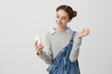 Portrait of woman 20s looking on screen of cellphone with pleasant wide smile. Charming female teenager making selfie portrait while listening music outside. Interaction concept