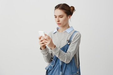 Puzzled young woman  frowning having problem with her gadget
