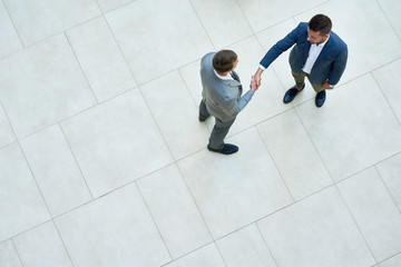 Top view of two business people shaking hands standing on tiled floor in hall of modern office building, copy space Fotoväggar