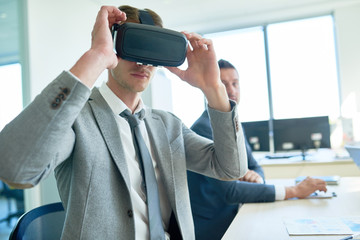 Portrait of young businessman using VR glasses during meeting in board room, copy space