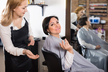 Hairdresser listens to wishes of adult woman about her hairstyle