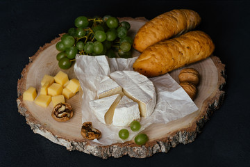 Cheese Camembert, bread, nuts and fruit on old wooden board. Food for wine and romantic, cheese and bread delicatessen. Menu design horizontal, side view.