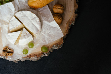 Tasting cheese dish with nuts and fruits on black table. Food for wine, cheese delicatessen. Menu design horizontal, top view.
