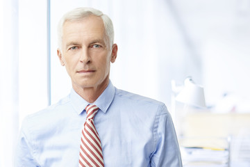 Financial business man. A senior financial consultant businessman standing in shirt and tie in his office.