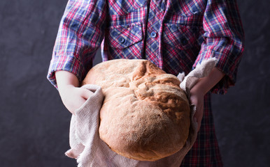 Little girl holding freshly baked crusty homemade ciabatta bread