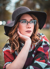 Pretty girl with glasses and hat  closeup portrait outdoors in the green park in autumn