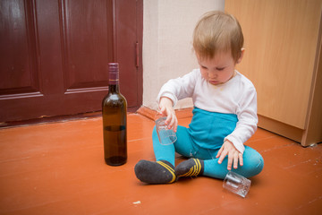 a little baby in dirty, torn clothes plays with a broken glass on the wooden floor, next to it there is a bottle with alcohol