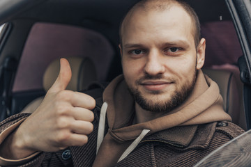 Smiling calm man sitting inside car showing thumbs up. Positive driver person