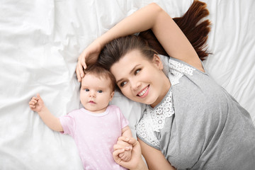 Young mother and cute baby on bed at home