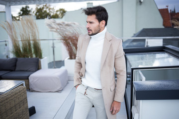 Handsome man in camel coat outside in windy day