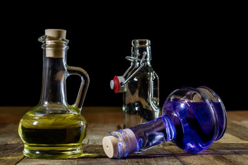 Bottles of colored liquid on a wooden kitchen table. Wooden table.