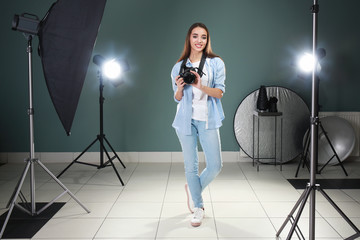 Beautiful young photographer in professional studio