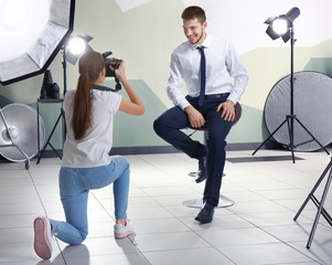 Young man posing for professional photographer in studio