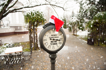 vintage street clock with title Merry Christmas New York and Santa Claus hat on them with falling snowflakes