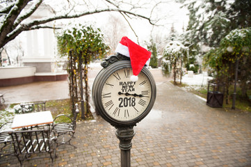 vintage street clock with title Happy New Year 2018 and Santa Claus hat on them in winter city park