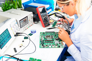 Female electronic engineer checking circuit board in laboratory