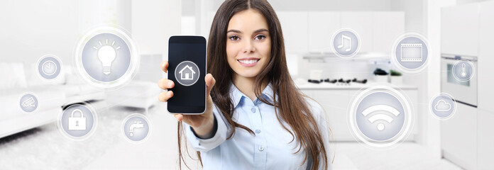 smart home smiling woman showing cell phone screen with symbols on kitchen and living blurred background
