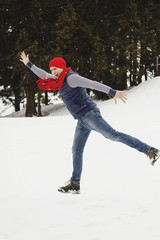 Young happy man standing on the top of mountain in snowy winter