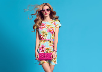 Fashion. Blond Woman in fashion pose. Young beauty Lady in Floral Dress Blowing lips. Trendy fashion Hairstyle, Glamour Pink Clutch. Playful Girl, Spring Summer Outfit Wall mural