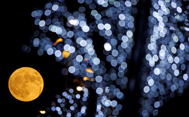 The full moon is pictured behind Christmas lights in Marseille