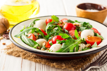 Fresh salad with arugula, cherry tomatoes, mozzarella cheese and walnuts on white wooden background.