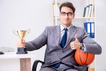 Businessman with prize cup for achievements in office