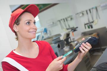 shopkeeper inserting a card in the machine