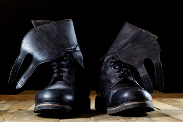 Old black Polish military boots on a wooden table.