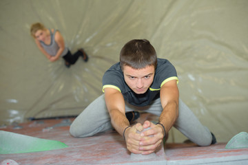 Downward view of man gripping climbing wall