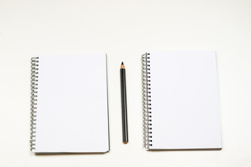 Sensual sketchbook and crayons on a white table. White table and white background.