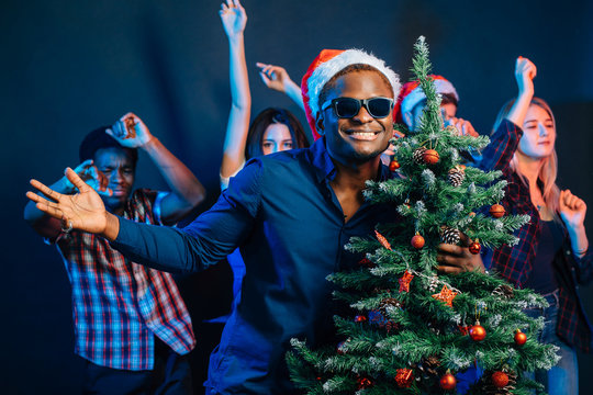 african american man hugging with cristmas tree and people dancing at background on new year party