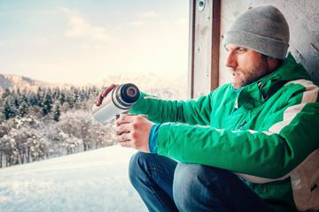 Man drinks a hot drink worker ot traveler on open winter air