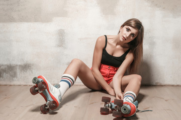 Sexy brunette girl sitting on the floor in roller skating.