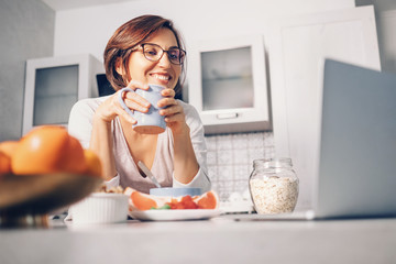 New day positive start - woman drinks a tea and watch laptop on the kitchen